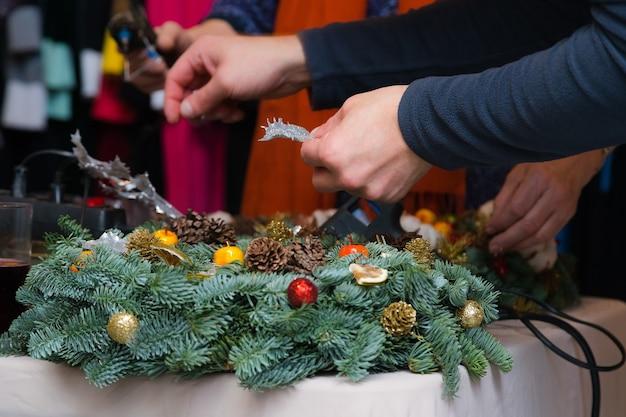 Мастерская по плетению рождественских венков. женские руки украшают праздничный венок из еловых веток, шишек и различных органических украшений на столе