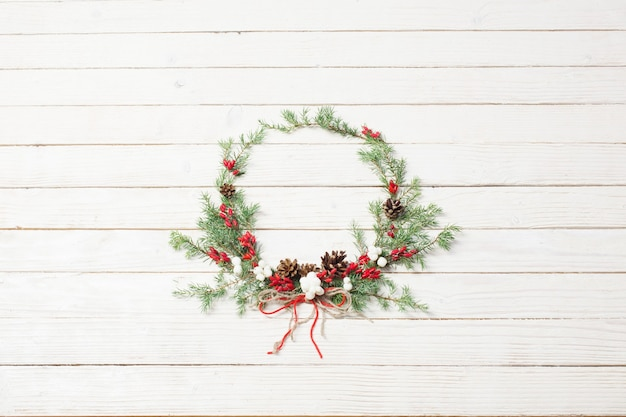 Christmas wreath on white wooden surface