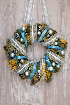 Christmas wreath with blue and silver decorations on wood