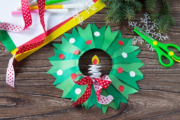 Christmas wreath with a candle on a written wooden table