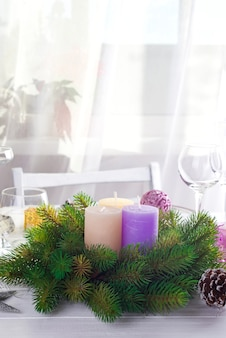 Christmas wreath with colorful big candles on a table