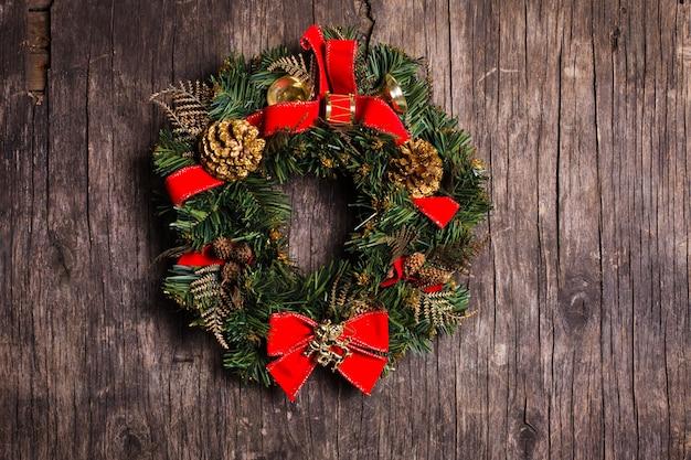 素朴な木製の背景に装飾が施されたクリスマスリース