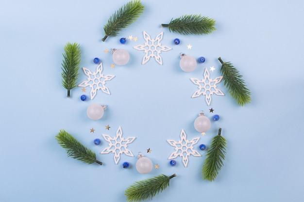 パステルブルーの背景にモミの枝と雪片とクリスマスリース。雪片の花輪の装飾が施された装飾品