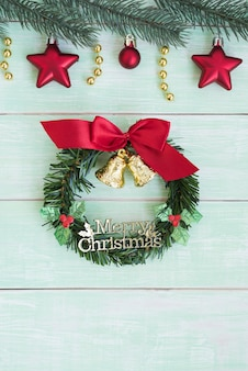 Christmas wreath with golden bells and red ribbon bow vertical