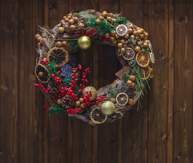 Christmas wreath with holly berry and dry orange slice hanged on the door