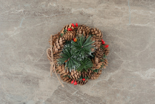 Christmas wreath with red beads and cones on marble.