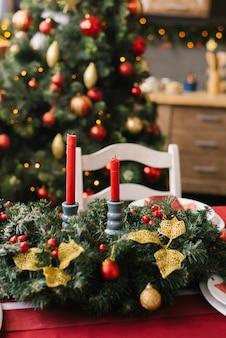 リビングルームやダイニングルームのテーブルに赤いキャンドルとクリスマスリース