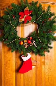 문에 빨간 양말이 달린 크리스마스 화환