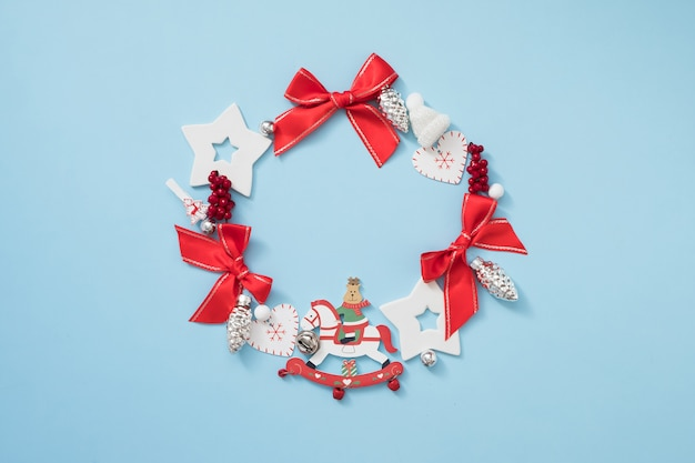 Christmas wreath with red and white decorations on pastel blue background. new year concept.