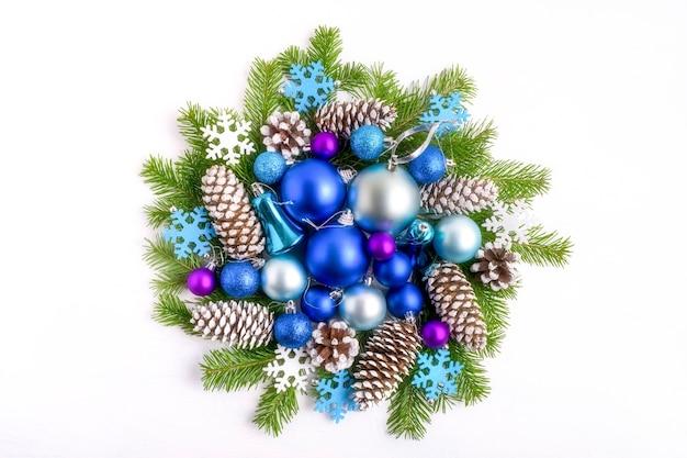 トウヒの枝と円錐形のクリスマスリースと青い色合いの装飾品