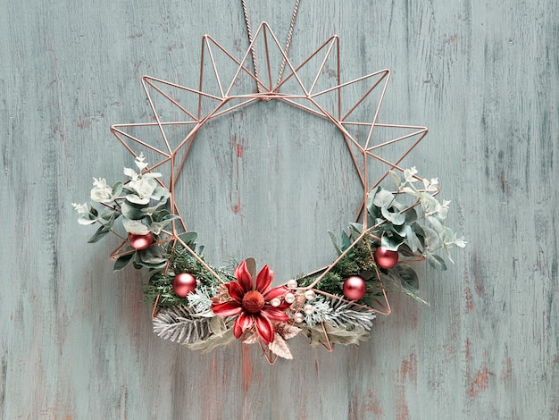 Christmas wreath with winter green leaves and flowers on geometric golden metal frame on rustic wooden door