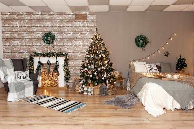 겨울 휴가 축하를 위해 장식된 침실의 벽에 크리스마스 화환이 있습니다. 축제 가정 장식입니다.