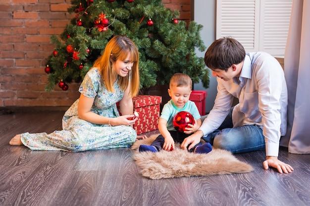 Рождество, рождество, семья, люди, концепция счастья - счастливые родители играют с симпатичным мальчиком