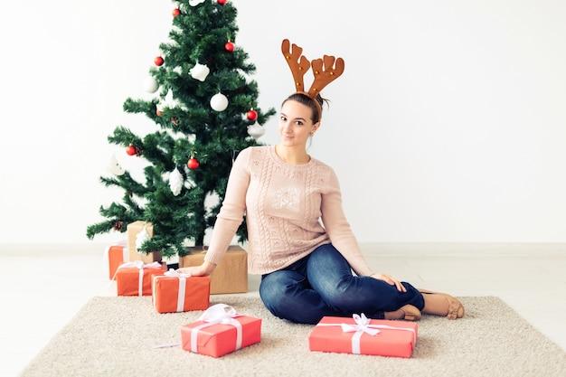 クリスマス、クリスマス、冬、幸福の概念-女の子はクリスマスツリーの背景にギフトを開きます。クリスマスを祝う幸せな若い女性