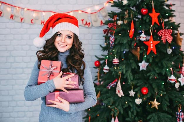 クリスマス、クリスマス、冬、幸福の概念-ギフトボックス付きサンタクロースヘルパー帽子で笑顔の女性