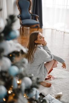 Рождество, рождество, зима, концепция счастья - улыбается женщина с множеством подарочных коробок. девушка открывает подарок на фоне елки. счастливая молодая женщина празднует рождество