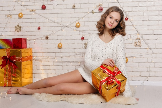 Christmas, x-mas, winter, happiness concept - smiling woman with many gift boxes. new year and christmas. woman holds a lot of gifts near a christmas tree.