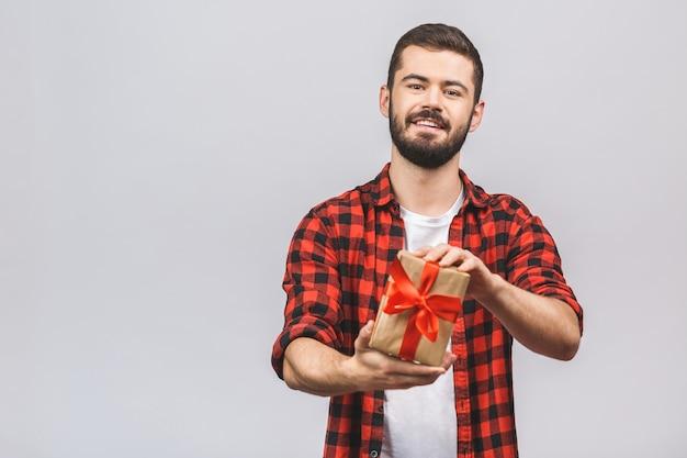Рождество, рождество, зима, день валентинки, день рождения, концепция счастья - усмехаясь человек в красной рубашке при подарочная коробка изолированная против белой предпосылки.