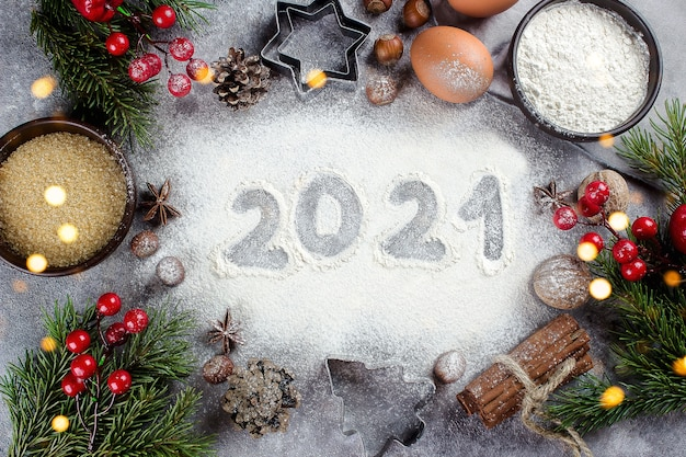 Christmas xmas card. 2021 text made by flour with bakery ingredients - eggs, brown sugar, cinnamon and festive christmas decoration on table.
