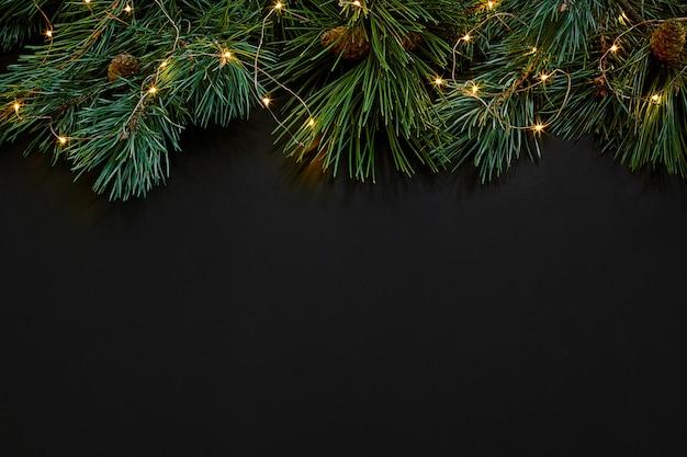 クリスマス。黒の背景の上面図にクリスマスのおもちゃとトウヒの枝。スペースをコピーします。静物。フラットレイ。新年