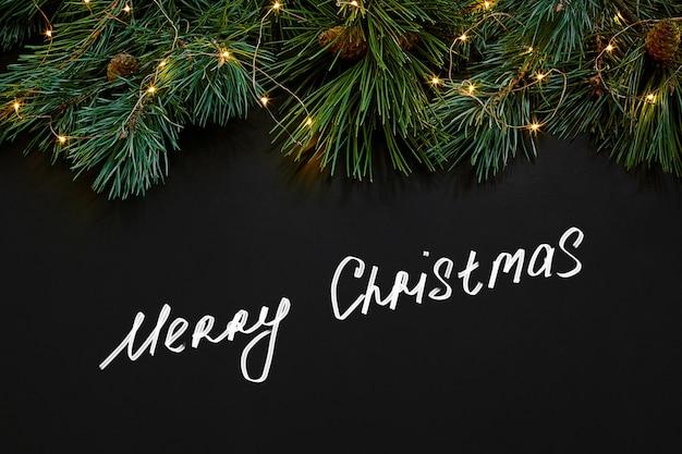 クリスマス。黒の背景の上面図にクリスマスのおもちゃとトウヒの枝。スペースをコピーします。静物。フラットレイ。