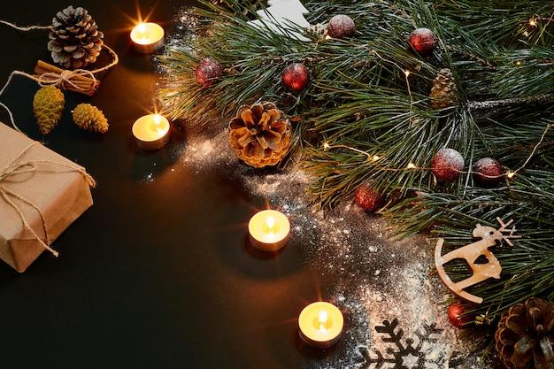 ろうそくとトウヒの枝を燃やすクリスマスクリスマスおもちゃ黒の背景にテキストのトップビュースペース