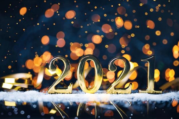 Рождественский год из золотых чисел с золотым блеском боке на темно-синей поверхности