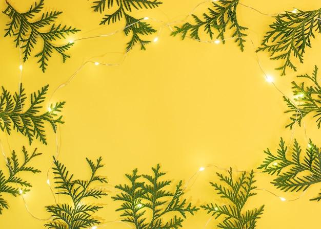 Рождественский желтый фон с рамкой из зеленых ветвей туи