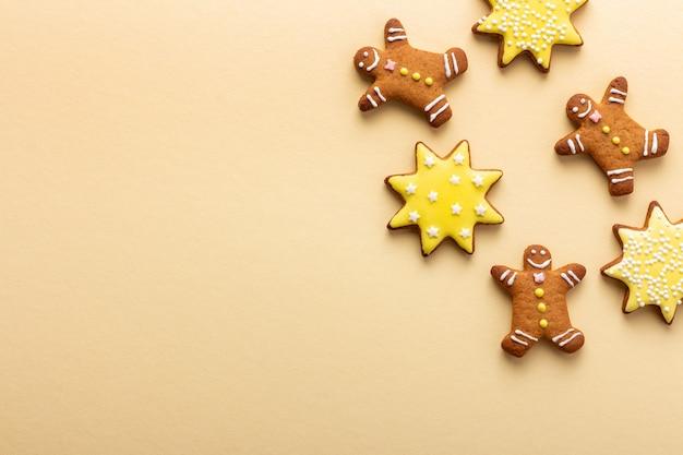 Рождественский желтый фон со счастливыми пряниками в форме человека и звездами с глазурью