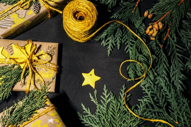 Christmas yellow handmade gift boxes on black background top view. merry christmas frame. winter xmas holiday theme. happy new year. flat lay.
