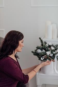 Рождество молодая девушка трогает новогодний букет макияж здоровая прическа с новым годом