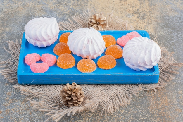 Christmas zephyr with jelly candies on a blue plate. high quality photo