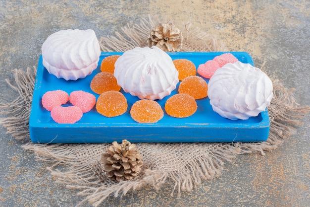 Рождественский зефир с желейными конфетами на синей тарелке. фото высокого качества