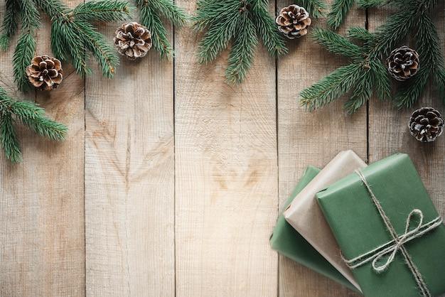 Рождественский фон с нулевыми отходами с подарочными коробками, еловыми ветками и сосновыми шишками