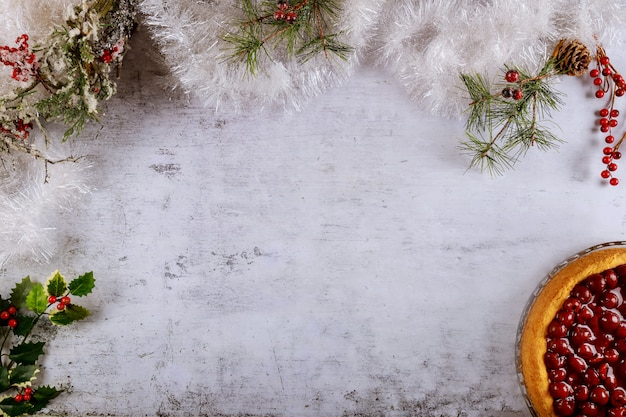 Christmass surface with berries cake and christmas tree branches