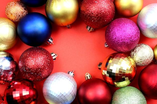 ボールの形をしたクリスマスツリーの色とりどりの明るいおもちゃは、赤の円の中にあります。フラットレイ