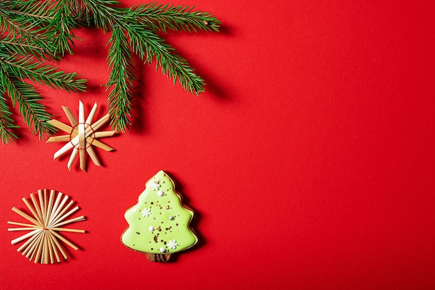 Рождественские украшения для печенья и еловые ветки на красном фоне