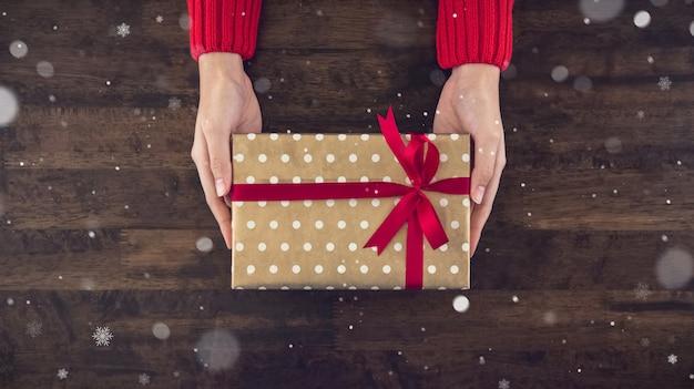 Руки женщины давая взгляд сверху подарочной коробки christsmas на деревянном столе