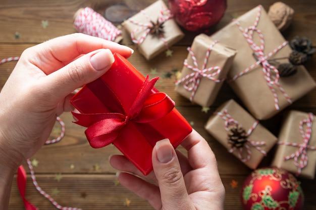 クリスマスギフトボックスを包む女性の手を保持しています。クラフト紙、赤いつまらないもの、木製のテーブルにキラキラに包まれたギフトボックスのグループ。 chritsmasフラット横たわっていた背景。