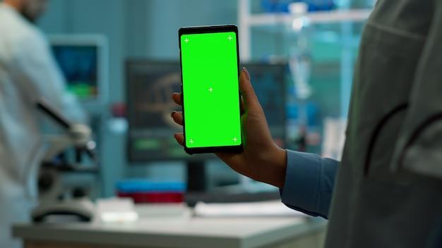 研究室のキャビネットの科学者の女性と白衣を着た同僚が血液サンプルを持って使用するスマートフォンのクロマキー分離ディスプレイ。モックアップの緑色の画面で携帯電話を使用している科学者