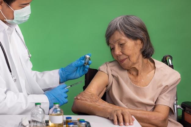 Chroma key, nurse doing vaccine injection to senior woman.