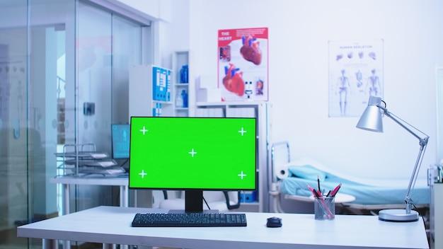백그라운드에서 의료진과 함께 병원 캐비닛의 컴퓨터에 크로마 키. 클리닉 캐비닛에 있는 의학 전문가의 디스플레이에 공백 및 복사 공간이 있는 컴퓨터.