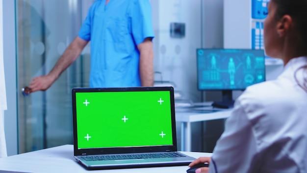 白衣を着た医師と青い制服を着た看護師が使用する診療所のラップトップのクロマキーは、キャビネットのガラスドアを開けています。メディで展示されているコピースペース付きのノートブックを使用して制服を着たメディック