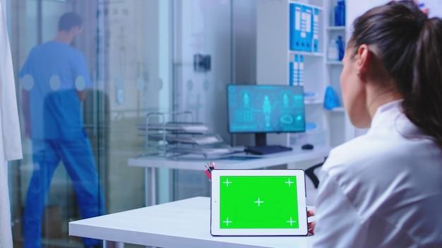 병원 캐비닛에 있는 의사와 파란색 유니폼을 입고 병원을 떠나는 간호사가 사용하는 태블릿 pc 디스플레이의 크로마 키. m을 하는 교체 가능한 화면으로 태블릿 컴퓨터에서 작업하는 건강 클리닉의 의사