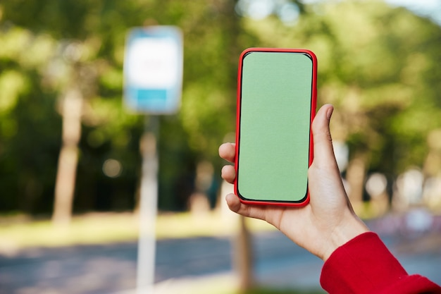 Chroma key phone in red case on bus stop, female arm holding green screen smartphone while waiting public transport