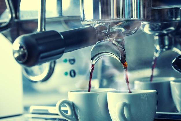 おいしいコーヒーを2つの白いカップに混ぜるクロームコーヒーメーカー。カップから蒸気が出てきています。