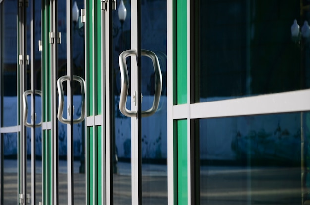 クロームドアハンドルとモダンなアルミニウムオフィスのファサードのガラス