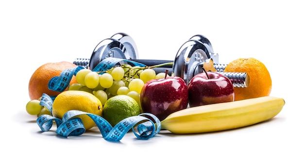 Хромированные гантели в окружении здоровых фруктов, измерительная лента на белом фоне с тенями. здоровый образ жизни, диета и упражнения.