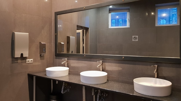 Chrome faucets with white round washbasins in a public toilet with a large mirror and gray walls, modern interior of a public toilet.