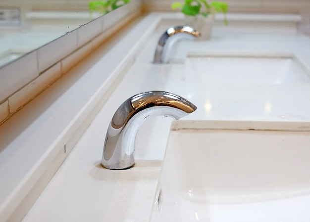 Chrome minimalist tap in restroom.